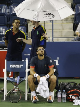 Janko Tipsarevic waits as play is suspended in his match with Philipp Kohlschreiber.