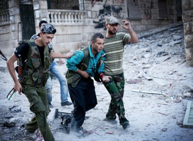 Free Syrian Army soldiers help a severely wounded fighter after he was shot by a Syrian Army sniper in the Izaa district of Aleppo, Syria
