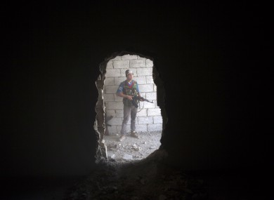Free Syrian Army fighter takes cover in a building during clashes against the Syrian Army in Aleppo today.