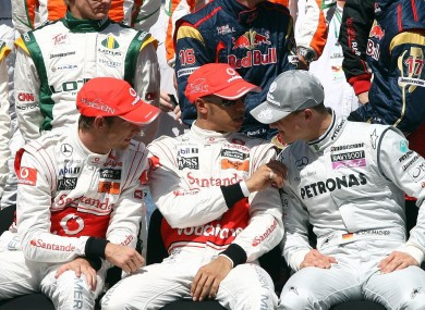 Lewis Hamilton and Jenson Button chatting with Michael Schumacher during the annual drivers team photo prior to the Gulf Air Bahrain Grand Prix at the Bahrain International Circuit yesterday.