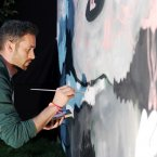 Artist Colm MacAthlaoich puts the finishing touches to his artwork in the festival's first Heineken beer garden near the main stage. (Laura Hutton/Photocall Ireland)