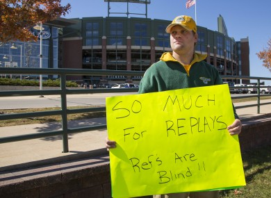 Green Bay Packers fan Mike LePak holds a sign in front of Lambeau Field on Lombardi Avenue yesterday.