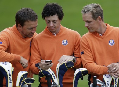 Europe's Graeme McDowell, left, and Luke Donald check TheScore app on Rory McIlroy's phone during the team photo. Probably.