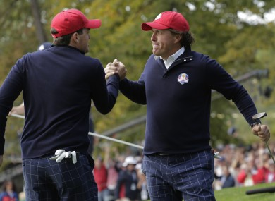 USA's Keegan Bradley congratulates Phil Mickelson after Mickelson made a putt to win the 13th hole.