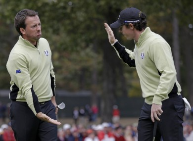 Europe's Graeme McDowell, left, is congratulated by Rory McIlroy after making a putt to half the 13th.