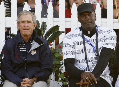 A regular odd couple: Former President George W. Bush and Michael Jordan watch as players tee off on the 13th hole yesterday.