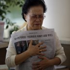 A woman holds an extra edition reporting about the death of the Rev. Sun Myung Moon at an Unification Church in Seoul, South Korea. Moon, self-proclaimed messiah who founded Unification Church, died Monday at a church-owned hospital near his home in Gapyeong County, northeast of Seoul, church officials said. He was 92. (AP Photo/Lee Jin-man)