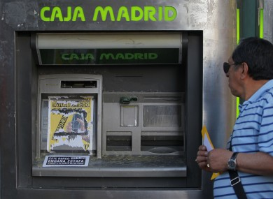 A man walks by a Bankia bank with its cash machine covered by a poster reading