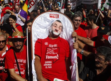 A man wearing a Mariano Rajoy mask plays dead during an anti-prosperity protest in Madrid.