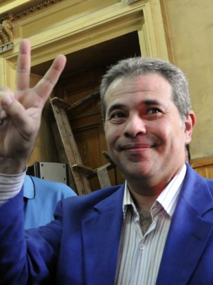 Tawfiq Okasha flashes the victory sign as he arrives in court in Cairo yesterday.