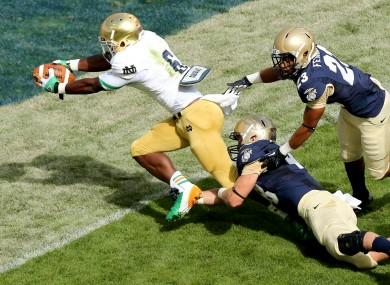 Notre Dame's running back Theo Riddick scores the opening touchdown despite Keegan Wetzel and Chris Ferguson of the Navy.