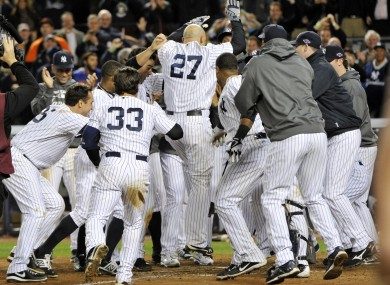 New York Yankees' Raul Ibanez (27) is mobbed by teammates at home plate after he hit the game-winning home run in the 12th inning.