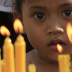 A Cambodian girl watches residents offer prayers to the late former King Norodom Sihanouk in front of Royal Palace in Phnom Penh, Cambodia. Hundreds of Cambodian villagers through widely provinces paid their respect and prayed for the soul of their former king on Sunday. (AP Photo/Heng Sinith)