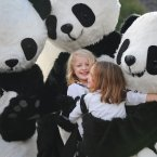 Sally and Sophie Shaw get a cuddle from the giant pandas. (Mark Runnacles/PA)