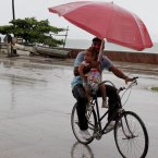 A man balances a child and umbrella on his bike as it rains during the approach of Hurricane Sandy in Manzanillo, Cuba, yesterday. 