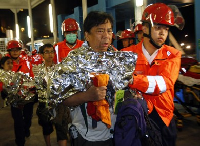 Survivors accompanied by rescuers, are taken onto shore after a collision involving two vessels in Hong Kong