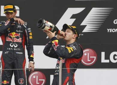 Red Bull driver Sebastian Vettel of Germany, centre, drinks champagne as he celebrates with teammate and second placed Mark Webber.