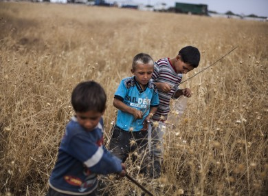 Syrian boys play near a refugee camp on the border with Turkey