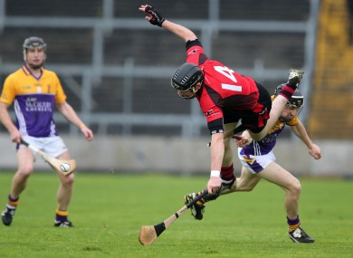 Oulart-The-Ballagh's Peter Murphy gets a hurl broke over his leg by JIm Berry of Faythe Harriers.