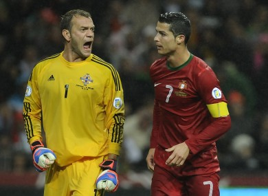 Northern Ireland's goalkeeper Roy Carroll, left, reacts as Portugal's Cristiano Ronaldo walks past during their World Cup Group F qualifying soccer match.