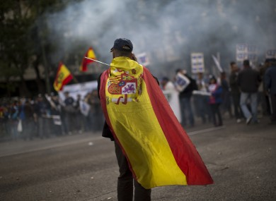 A police officer wearing a Spanish flag walks in front of a demonstration where other police officers protest by blocking the street in front of the Interior Ministry in Madrid, Spain, Saturday, Oct. 27, 2012.