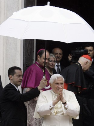 The pope's former butler Paolo Gabriele, at left holding umbrella.