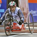 Former Formula One race car driver Alex Zanardi, who lost both legs in a crash in 2001, crosses the finish line in the men's handcycle category of the New York City Marathon in New York (AP Photo/Kathy Willens).