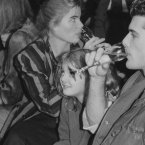 Actress Mariel Hemingway, left, sips from a glass while eyeing the crowd as actress Drew Barrymore, center, and her friend Bruce Thomas watch the fashions at Pat Kerr's show, held in New York's Hard Rock Cafe, November 1984. 