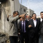 Tunisian Foreign Minister Rafik Abdessalem, center, visits Gaza's Hamas Prime Minister Ismail Haniyeh's demolished headquarters in Gaza City, today. Israel bombarded the Hamas-ruled Gaza Strip with more than 180 airstrikes early Saturday, the military said. The new attacks followed an unprecedented rocket strike aimed at the contested holy city of Jerusalem that raised the stakes in Israel's violent confrontation with Palestinian militants. (AP Photo/Hatem Moussa)