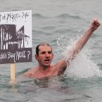 Swimmer Paul Wright  joins  protestors as they  gather at the 40 foot bathing pool in Sandycove to voice their safety fears for plans to allow exploration for oil in Dublin Bay off Dalkey. (Niall Carson/PA Wire)