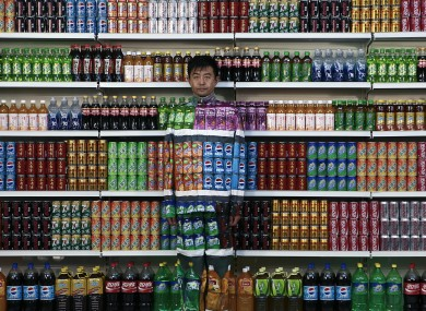 Chinese artist Liu Bolin waits for his colleagues to put a finishing touch on him to blend into rows of soft drinks in his artwork entitled