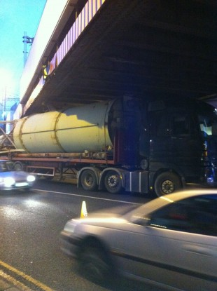 The truck stuck under the bridge