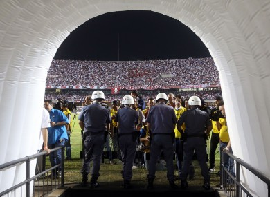 Police officers stand guard the entrance to Argentina's Tigre's dressing room after a fight among teams' members at the end of the first half.