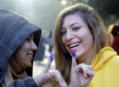Egyptians girls show their inked fingers after casting their votes at a polling station in a referendum on a disputed constitution drafted by Islamist supporters of President Mohammed Morsi in Cairo