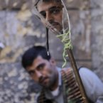 24 September: A Free Syrian Army soldier, foreground, looks at a mirror which helps him see Syrian troops on the other side, as he takes his position with his comrade in Aleppo. (AP Photo/Hussein Malla)