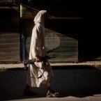 12 September: An FSA fighter walks through a street in the Bustan Al Qsar district in Aleppo. (AP Photo/ Manu Brabo)