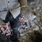 14 September: A Syrian man shows a torn picture of President Bashar Assad and his family. He found the pieces in the rubble of a government building, destroyed in a Syrian government airstrike earlier in the day. (AP Photo/Muhammed Muheisen)
