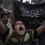 21 September: A Syrian shouts slogans against the regime in front of a flag of the armed Islamic opposition group, the Nusra front, during a demonstration in the Bustan al-Qasr neighborhood of Aleppo, Syria. Arabic from the Quran reads, 