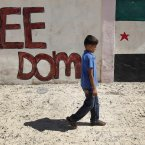 23 September: A Syrian boy walks in front of wall painted with colours of the Syrian revolutionary flag in Marea village on the outskirts of Aleppo. (AP Photo/Hussein Malla)