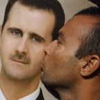 4 January: A pro-Syrian regime protester kisses a portrait of Syrian President Bashar Assad. (AP Photo/Muzaffar Salman)