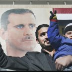 20 January: A pro-Syrian regime protester, holds his son as they flash a victory sign in front a giant portrait of Syrian President Bashar Assad during a demonstration to show their solidarity for their president, in Damascus. (AP Photo/Bassem Tellawi)