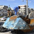 21 February: Syrian girls play on top of a destroyed Syrian riot police tank at Bayada in Homs. (AP Photo)