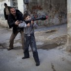 4 March: A man teaches Bilal, 11, how to use a toy rocket propelled grenade in Idlib. (AP Photo/Rodrigo Abd)