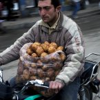 6 March: A man rides his motorcycle after buying potatoes in a street market in Idlib, north Syria. (AP Photo/Rodrigo Abd)