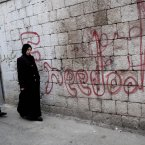 11 March: Two Syrian women walk past graffiti that reads 'freedom' in Idlib, north Syria. (AP Photo/Rodrigo Abd)
