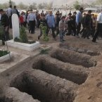 5 April: Mourners walk past open graves at a cemetery during the funeral for four people killed in a raid by government forces in a neighbourhood of Damascus. (AP Photo)