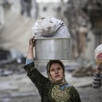 11 December: A Syrian woman and girl carry their belongings after their home was damaged due to fighting between Free Syrian Army fighters and government forces in Aleppo. (AP Photo/Narciso Contreras)