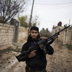12 December: A Free Syrian Army fighter poses as he carries his weapon in the northern province of Aleppo. (AP Photo/Manu Brabo)