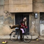 13 December: A rare moment of joy as a Syrian man smiles when climbing onto his bicycle in Maaret Misreen, near Idlib. (AP Photo/Muhammed Muheisen)