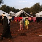 13 December: Syrian children, who fled their home with their families in Hama due to government airstrikes, stand next to their tent at a camp for displaced Syrians in the village of Atmeh. (AP Photo/Muhammed Muheisen)